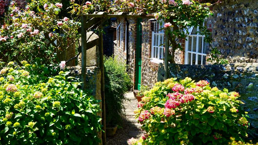 garden with garden path, trellis archway and flowers in flowerbeds.